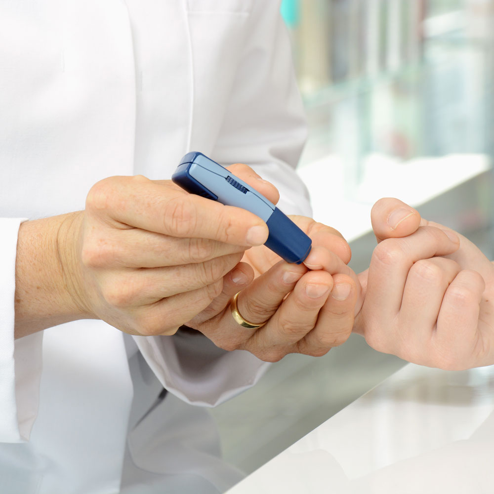 pharmacist administering diabetes test on patient's finger