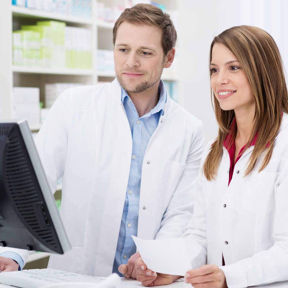 smiling male and female pharmacists looking at computer
