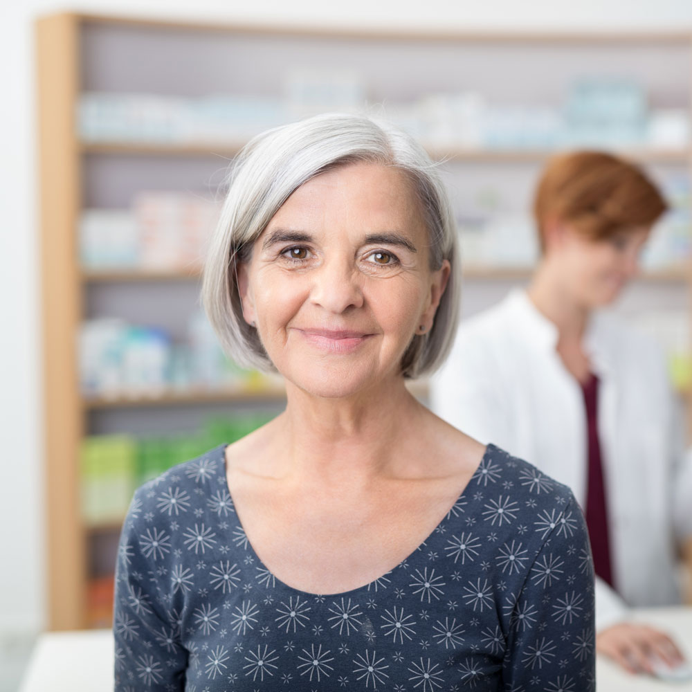 smiling older grey-haired patient at pharmacy