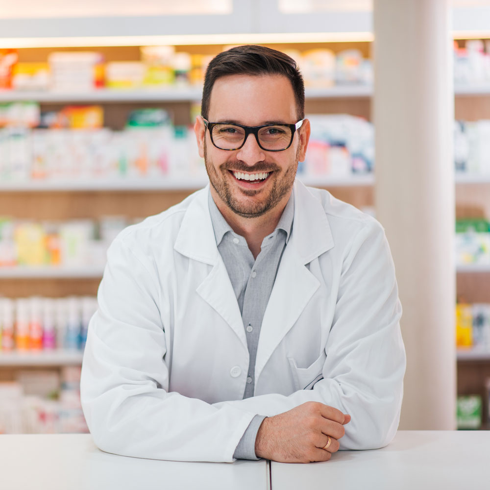 smiling male pharmacist looking at camera