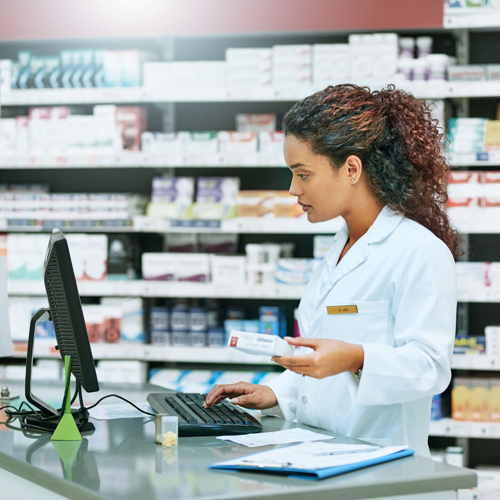 pharmacist holding medicine looking at computer