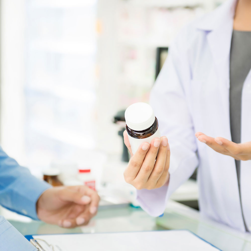 close up of pill bottle in pharmacist hand