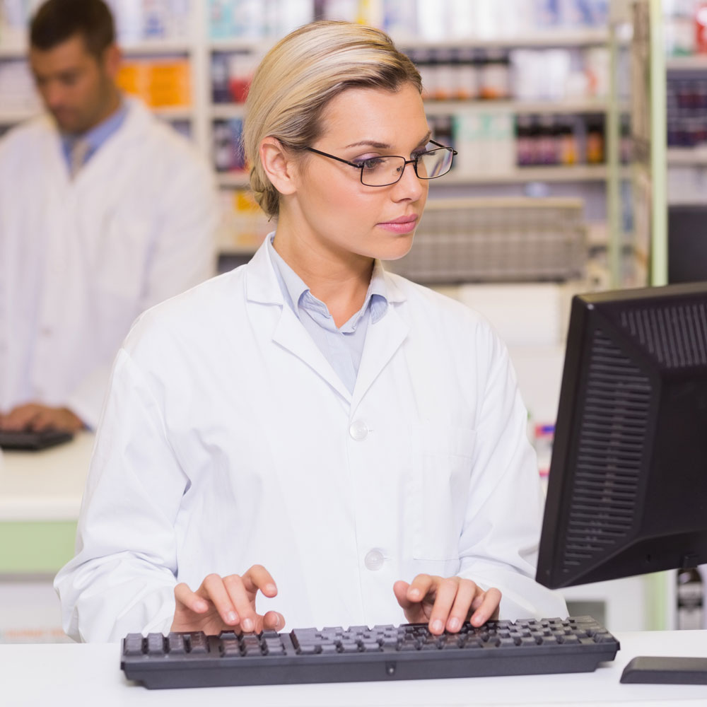 female pharmacist typing at computer