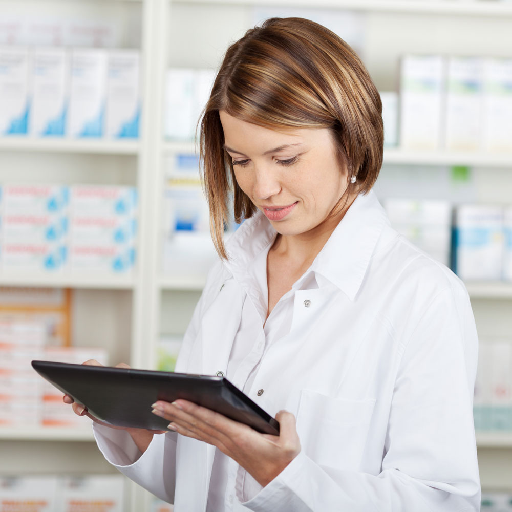 female pharmacist holding and looking at ipad