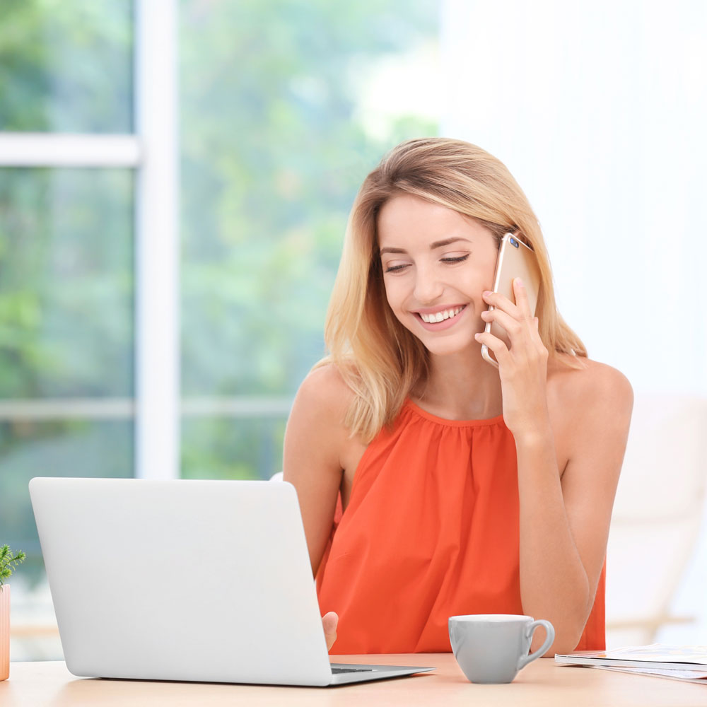 smiling blonde woman on cell phone looking at laptop